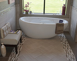 This bathroom has a modern feel created by a geometric multi tiled rug. The space is softened with the addition of this free standing curvilinear tub from Bain Ultra.