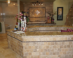 This Roman tub makes a grand statement. It is lined with travertine and a bronzed pencil piece.